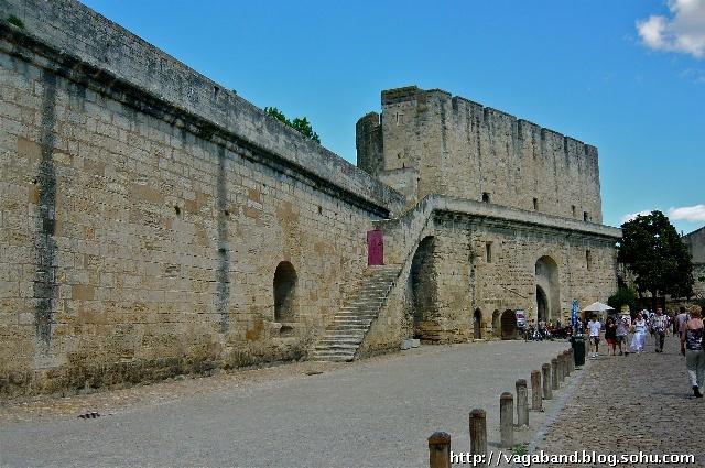 """来到法国艾格莫尔特(Aigues-Mortes),一道宏伟高大的城墙和一处圆柱尖顶塔楼呈现在眼前,这是法国保存最完整的古城墙之一。进入古堡式的城门,笔直的街道,整齐的小楼,好像由大型积木搭建的道具,无怪乎人们称这里是中世纪的 """"试管之城"""" (Retortenstadt)。艾格莫尔特始建于公元前一零二年,公元十三世纪中叶,这里是法国当时唯一的地中海港口,由于城市发展扩建部分远离城墙之外,才使古城一直保持着原始状态。一千六百五十米长的古城墙于公元十三世纪末完工,共有五大五小十个城门,三"""